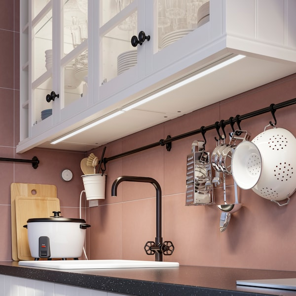 A black water tap in front of a pink wall.