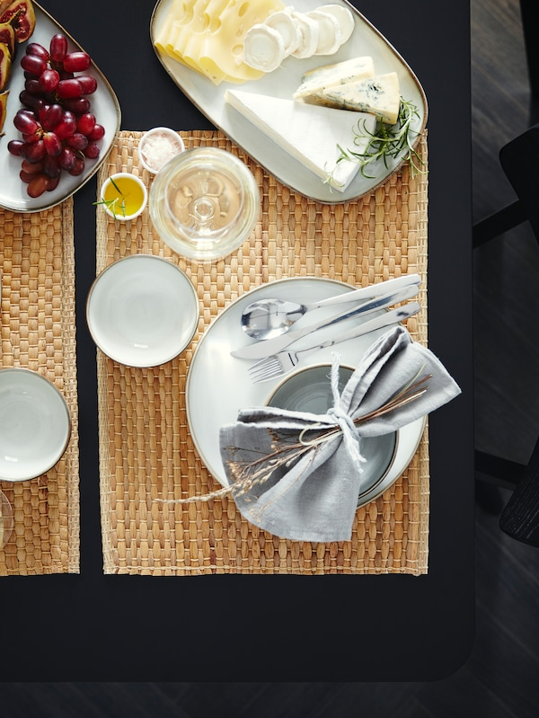 Pöytä, jossa vesihyasintista valmistettuja tabletteja, valkoinen astiasto, tarjolla juustoa ja viinirypäleitä.