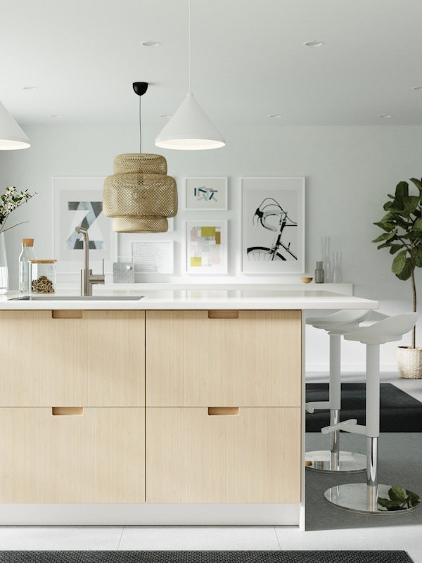 A kitchen island with a worktop in marble effect and drawer fronts in bamboo, two white bar stools and pendant lamps.