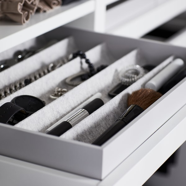 Light grey KOMPLEMENT insert with compartments containing small items like makeup and jewellery in a white pull out tray.