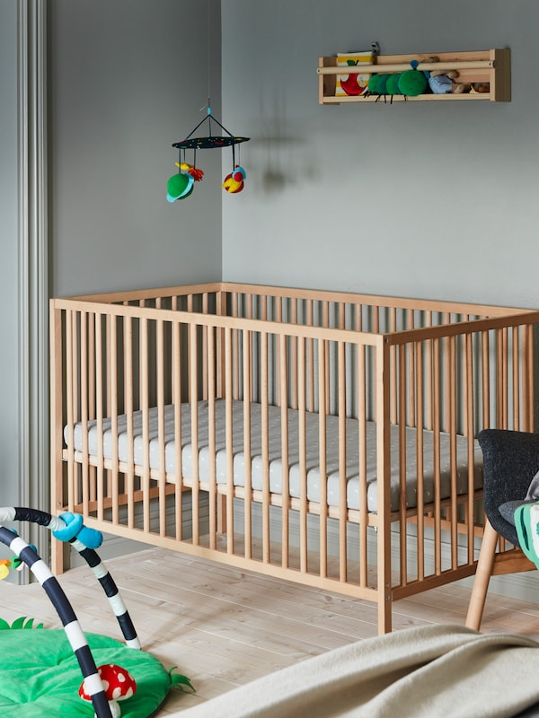 A SNIGLAR cot stands in a corner with a KLAPPA mobile hanging above it. A KLAPPA baby gym lies on the floor nearby.