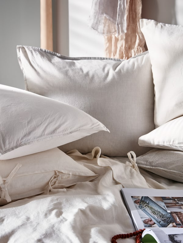 A lot of different kinds of pillows sit on a bed. An open book of colourful cartoons lies on the bed near the pillows.