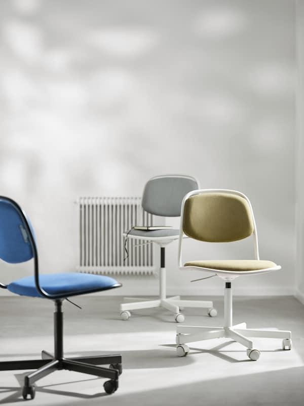 Divisão com três cadeiras giratórias ÖRFJÄLL, uma em branco e cinzento claro, outra em branco e amarelo esverdeado e outra em preto e azul.