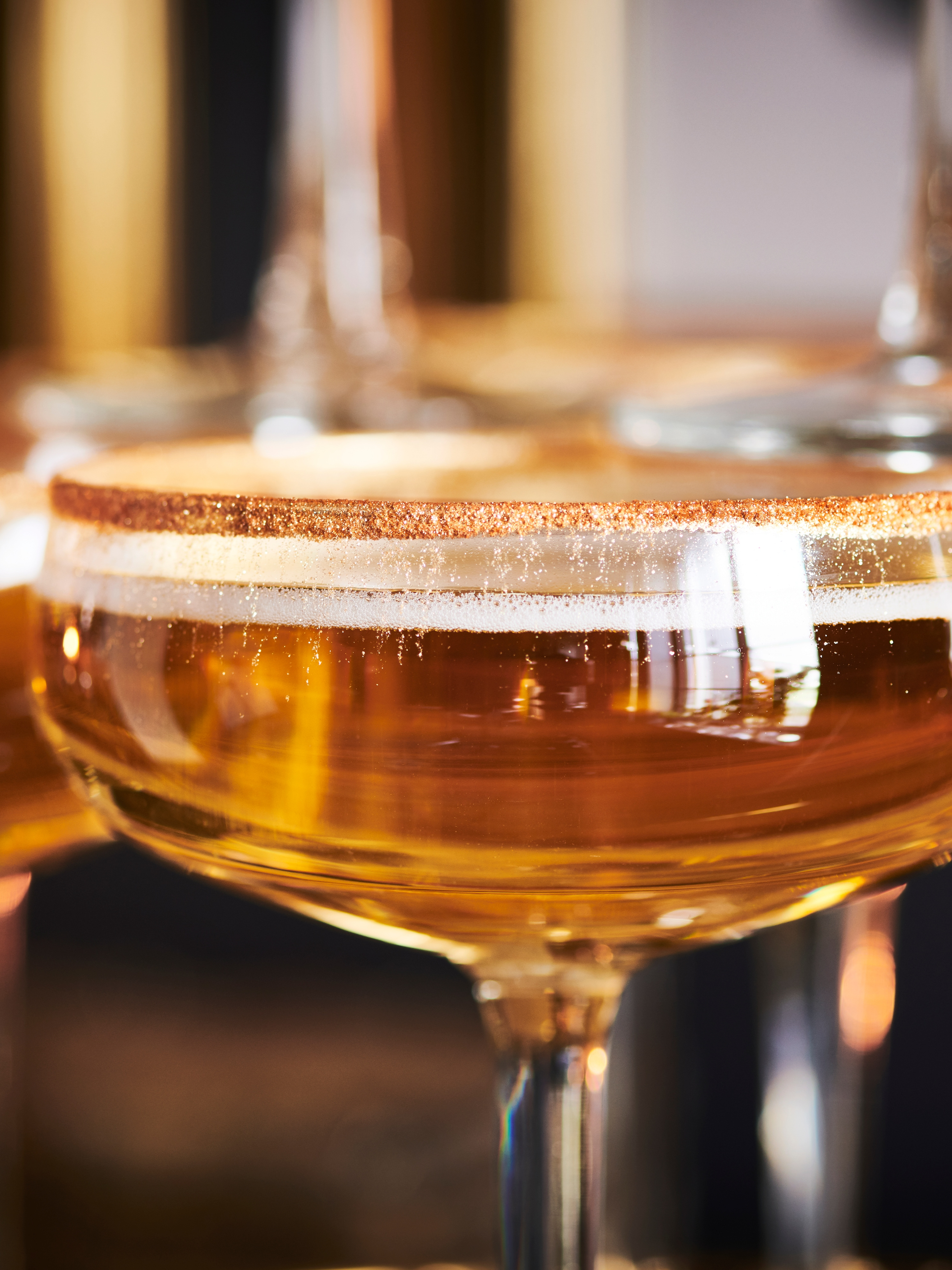 A close-up of STORHET champagne coupe shows it is filled with an amber-coloured liquid and has edible gold on its rim.
