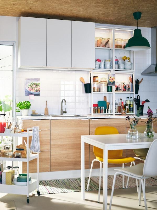 Valoisa ENHET-keittiö, jonka yläkaapit ovat valkoiset ja alakaapit puunväriset. Keittiössä on valkoinen MELTORP-pöytä jonka ääressä on keltainen LEIFARNE-tuoli.