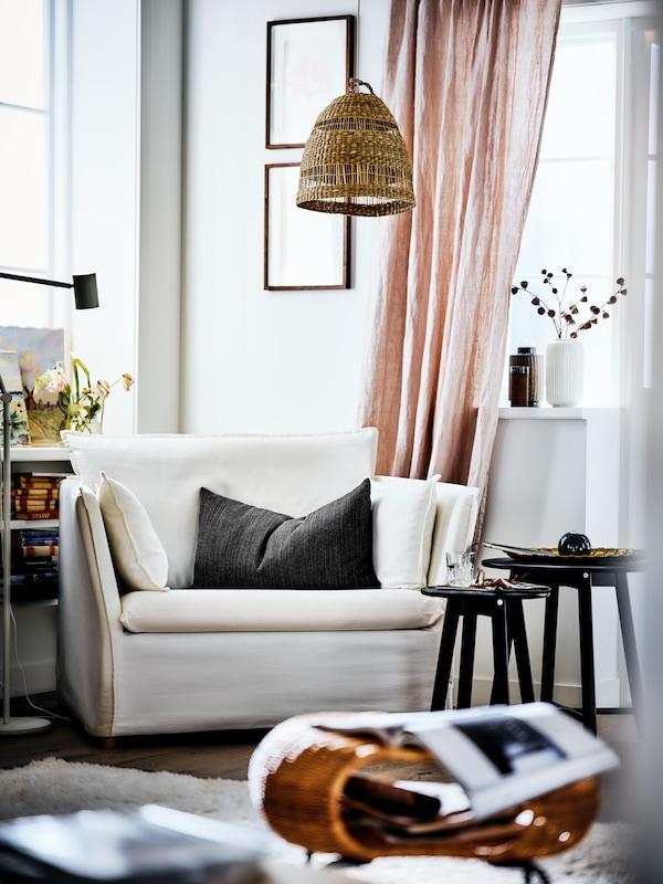 Un fauteuil BACKSÄLEN dans le coin d'un salon lumineux, une suspension au-dessus et des tables gigogne à côté.