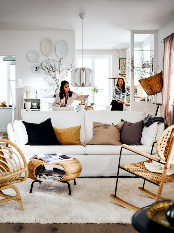 A white BACKSÄLEN sofa and two armchairs in a bright country-style living area with two women at the back of the room.