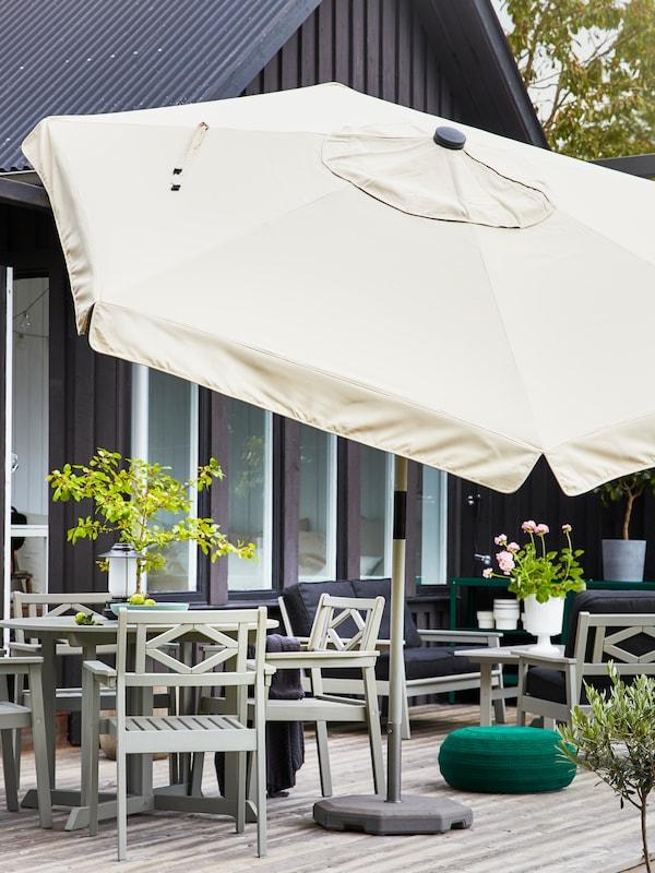 مظلةكبيرة بيج بجوارمساحةتناول طعام خارجيةمكونة من طاولة رماديوأربعة كراسي رمادي.