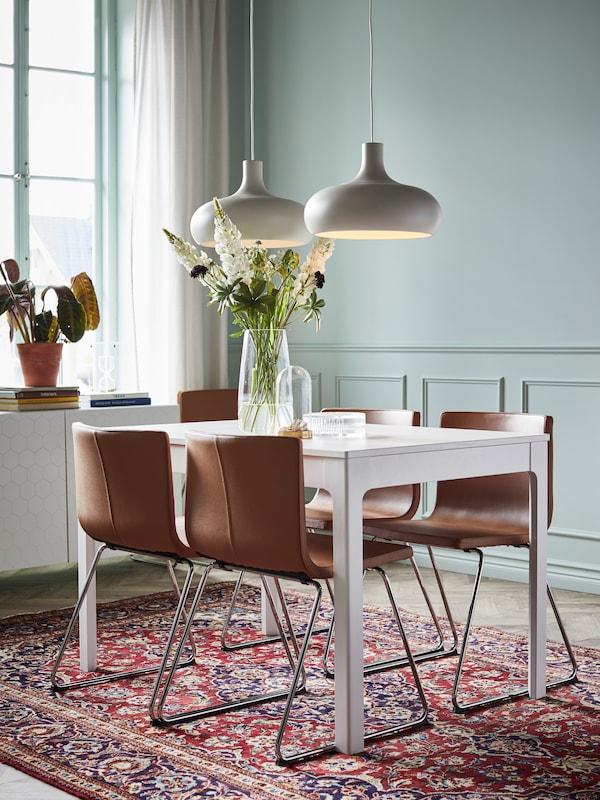Fyra stolar vid ett EKEDALEN matbord med en blomvas och vid ett fönster.