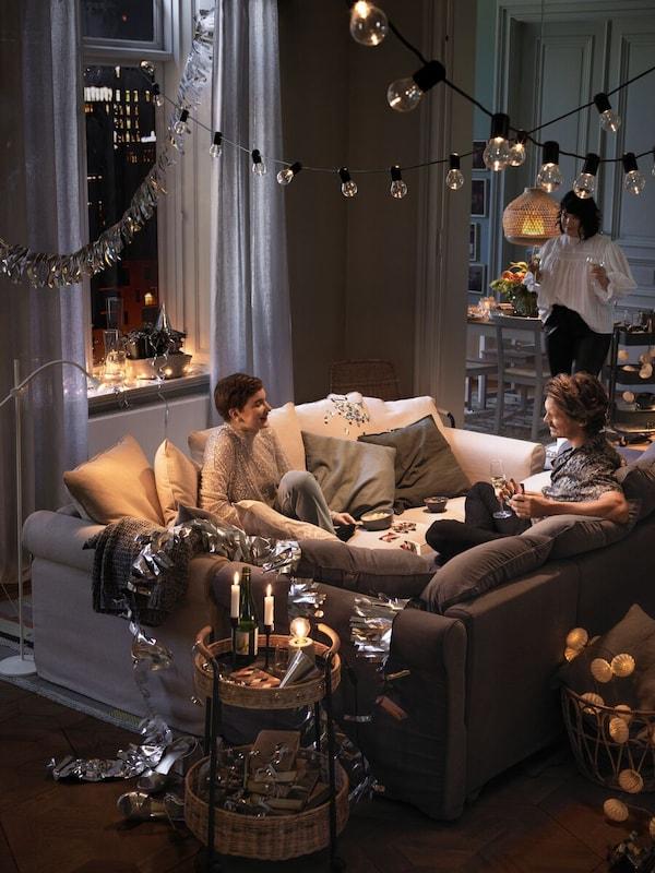 Twee mensen zitten tegenover elkaar op tegenover elkaar staande zitbanken. Een andere persoon staat ernaast. Bijzettafels met kaarsen, verlichting en decoratie.