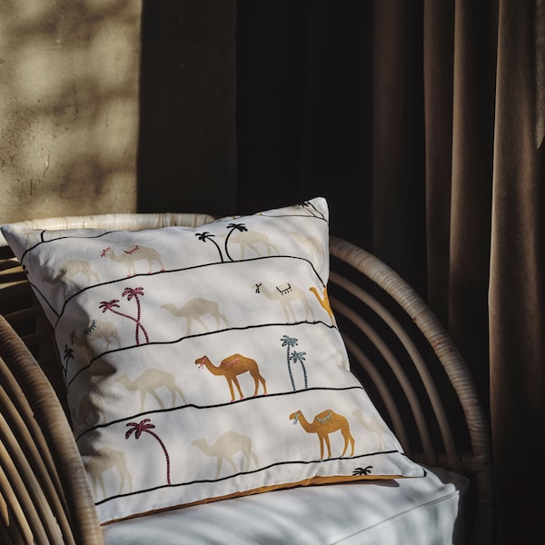 A cushion with a TILLTALANDE cushion cover with a camel pattern lies against the back of a chair.
