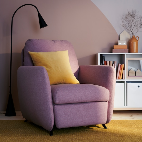 A living room with a pink recliner chair with a yellow pillow on it, a floor lamp, a white storage unit with books.