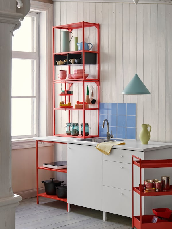 Some red-orange and white ENHET modules providing open and closed storage with colourful dinnerware in a kitchen.