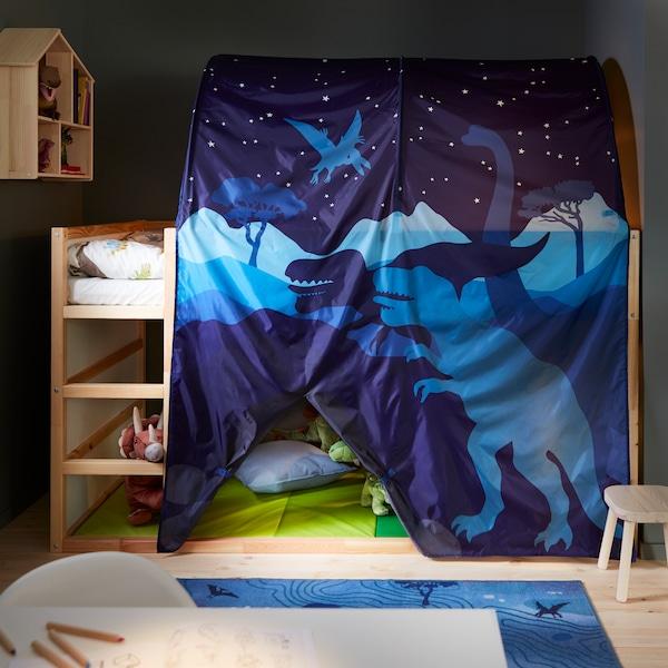 Een KURA dinosaurusbedtent die in een kinderkamer een KURA keerbaar bed in grenen en wit bedekt, met daaronder een zachte dinosaurusknuffel.