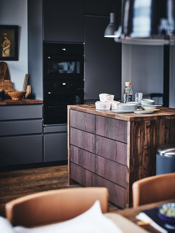 مطبخ METOD مع جزيرة مطبخ خشبية عليها أطباق وحافظات طعام للوجبات الجاهزة في الأعلى.