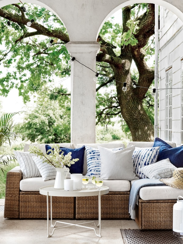 O canapea cu tapițerie albă și perne colorate și cu diferite modele împrăștiate este amplasată afară sub o ghirlandă luminoasă.