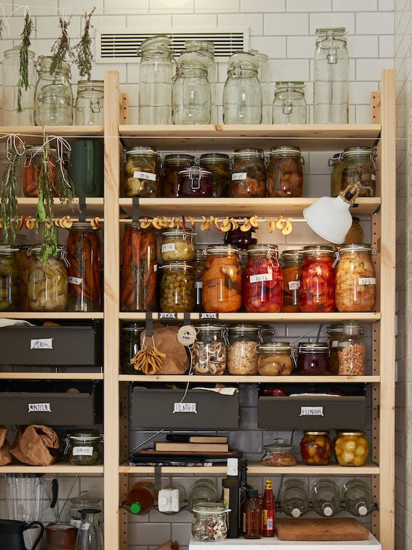A large wooden open shelving unit storing various kitchen items such as glass jars with lids containing preserved fruits.