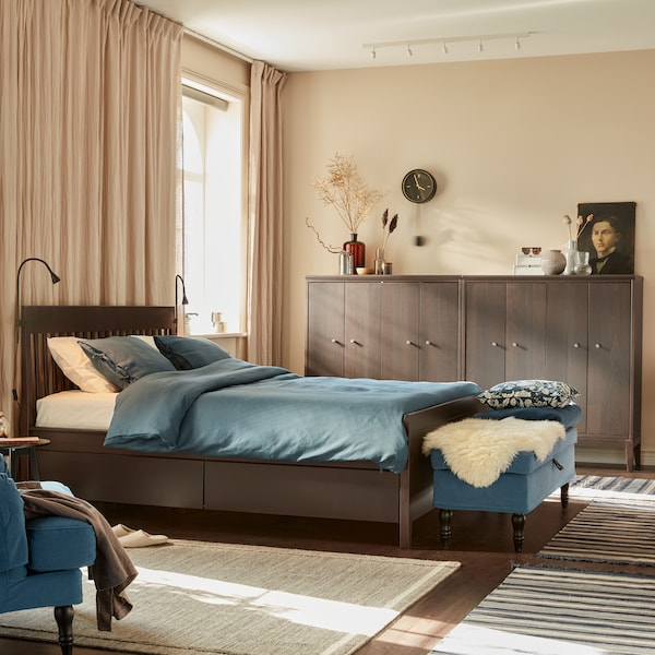 An IDANÄS bed with PUDERVIVA bed linen stands in a bedroom that has a window treatment including floor-length curtains.