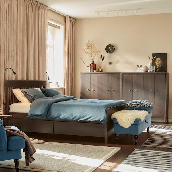 Letto TUFJORD con biancheria KUNGSBLOMMA e accanto un comodino in una camera da letto con pareti in legno.