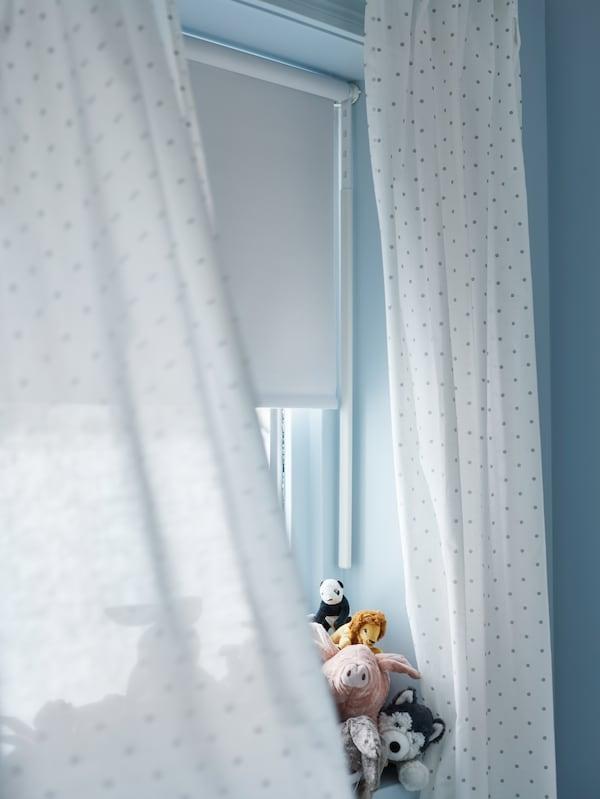 Une fenêtre avec des peluches sur le rebord, des rideaux à points blancs LEN et un store à enrouleur opaque blanc FRIDANS.