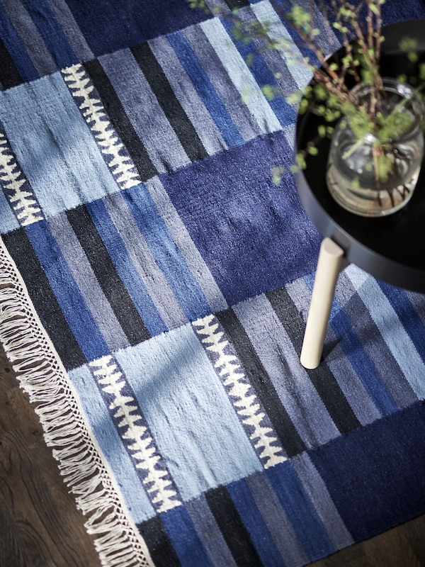 A rug in various shades of blue, black, gray and white, with a coffee table holding a few plant cuttings in a glass jar.