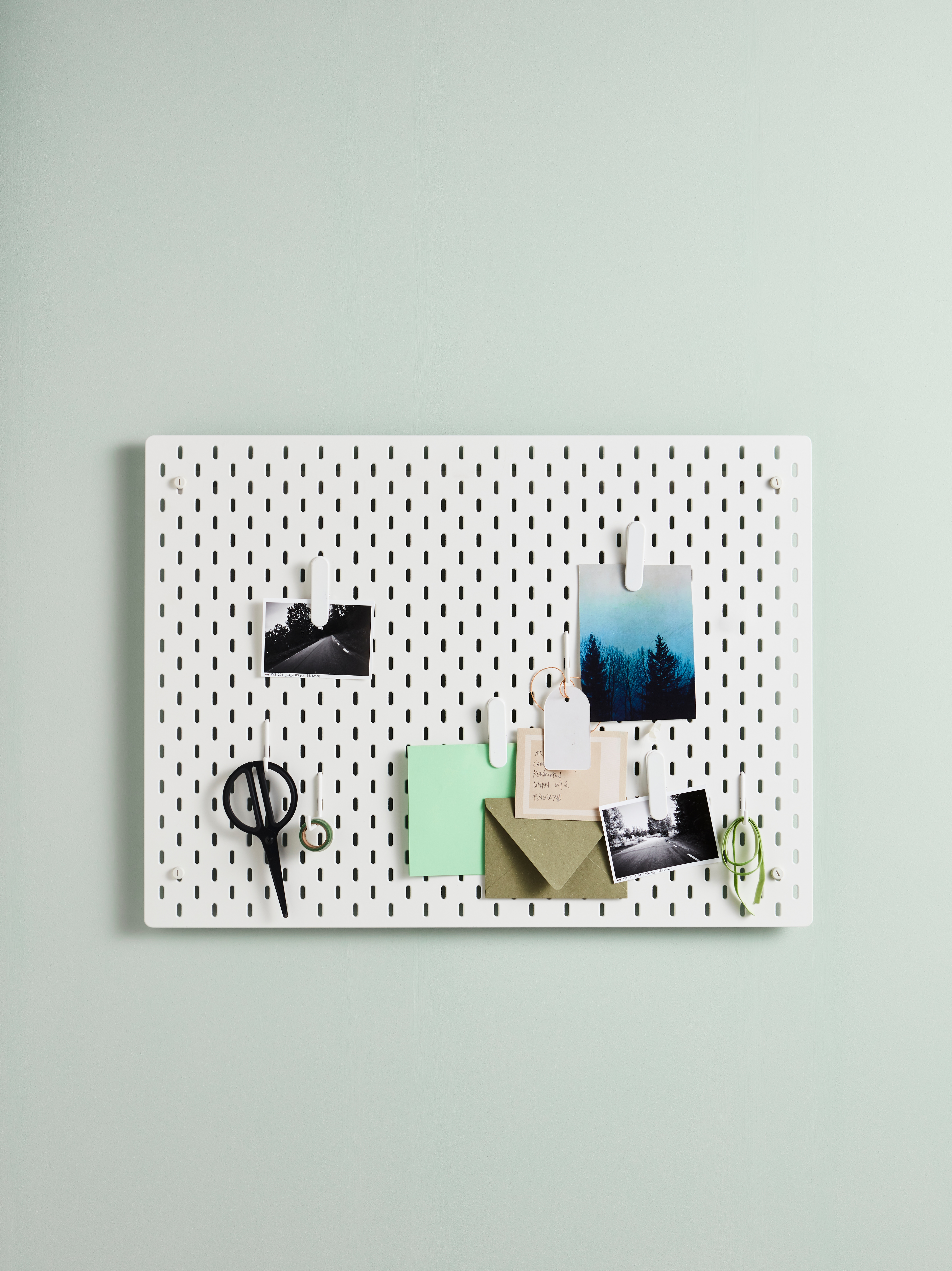 A white SKÅDIS pegboard is on a light green wall. Clips and hooks on the pegboard hold scissors, photos and envelopes.