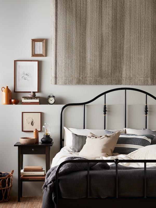 Egy hálószobában járunk, ahol szürke-bézs ÄNGSLILJA ágyneművel kiegészített fekete SAGSTUA ágyat, egy faliszőnyeget és egy HEMNES éjjeliszekrényt látunk.