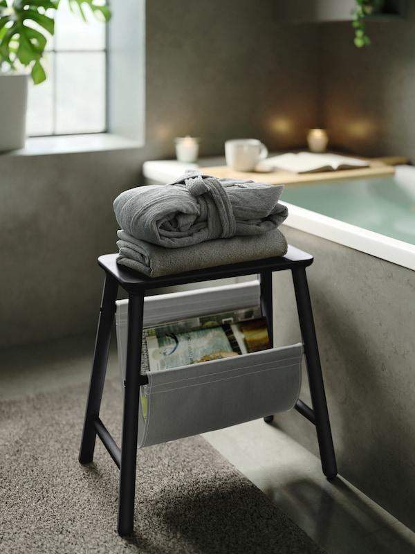 روب حمام رمادي ROCKÅN مطوي بعناية فوق منشفة رمادية على كرسي خشبي بجوار حوض الاستحمام وهناك صينية فوقه.