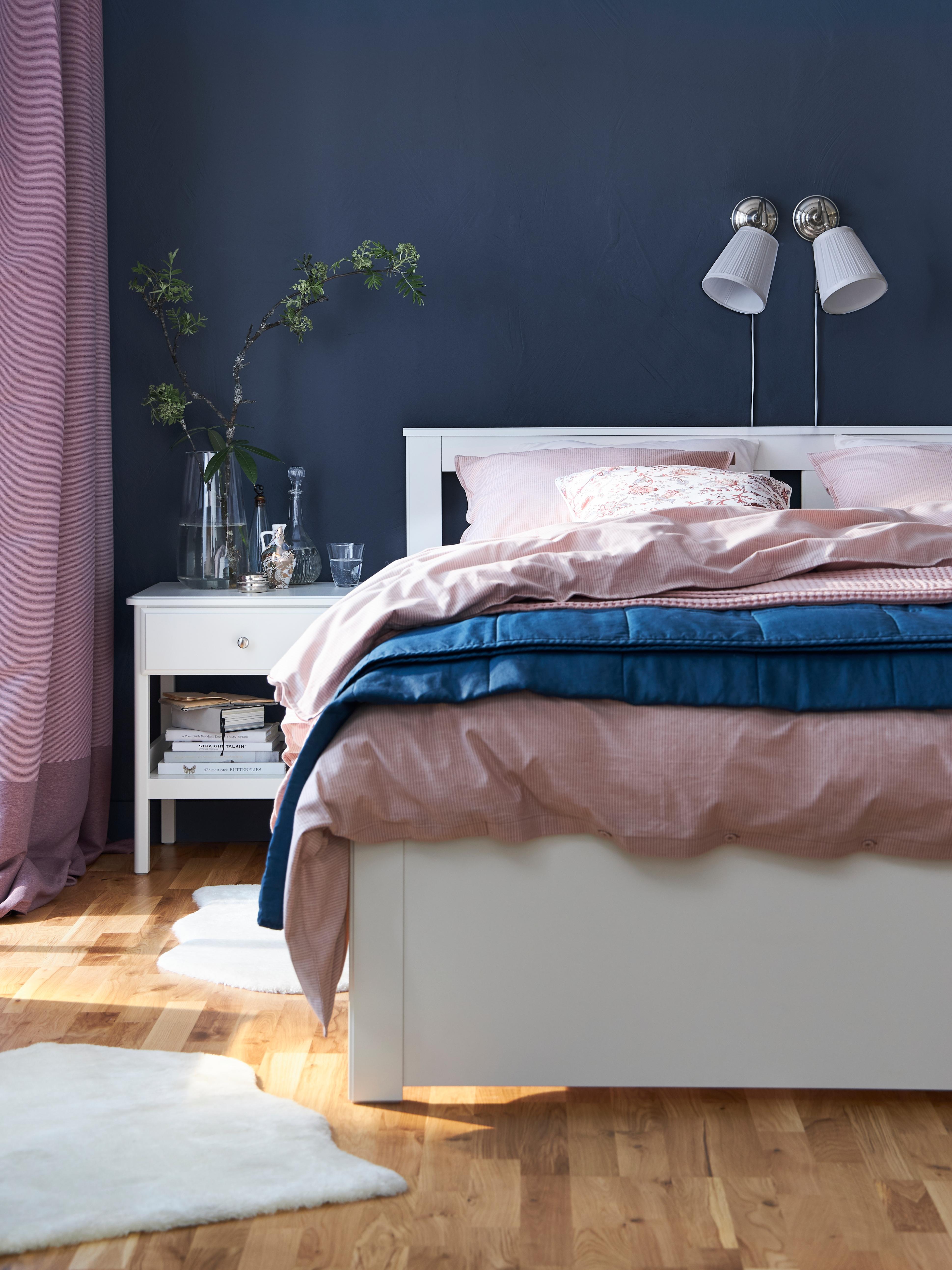 Struttura letto SONGESAND bianca con biancheria blu e rosa e tappeti bianchi, in una stanza con il pavimento in legno.
