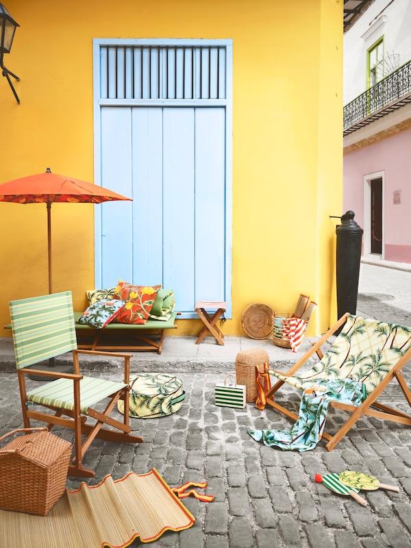 Mecedora y tumbona plegables con estampados y dibujos en verde, en una calle de adoquines.