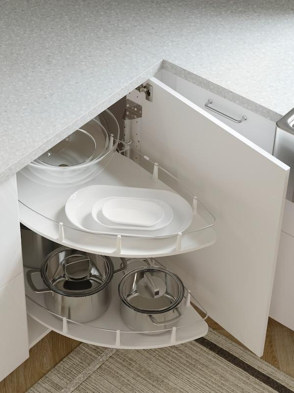 Prikaz kuhinje sa sivom kuhinjskom radnom pločom i otvorenim kutnim podnim elementom bijele boje s UTRUSTA izvlačnim umetkom na kojem se nalaze lonci, tave i posuđe,