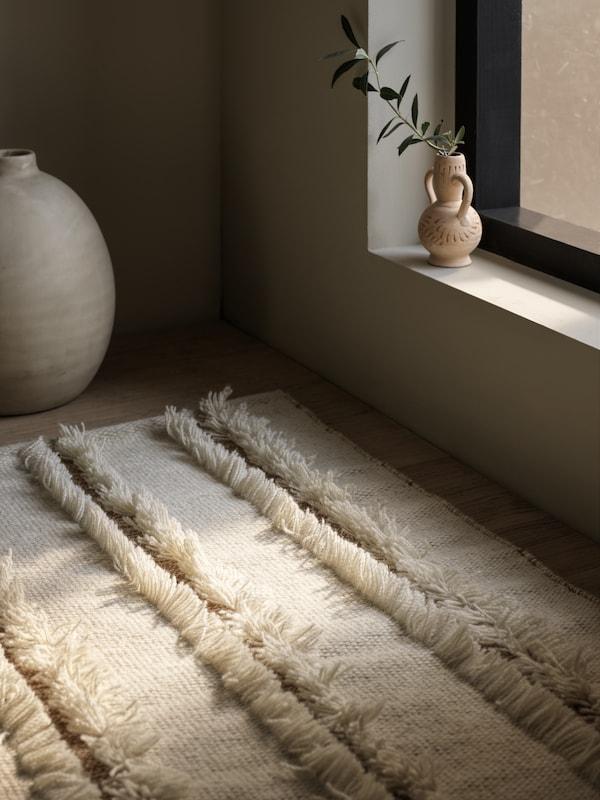 Ein flach gewebter PEDERSBORG Teppich liegt vor einem Fenster, durch das warmes Sonnenlicht auf den Teppich fällt.