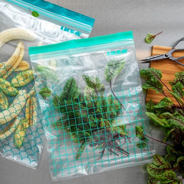 Dos bolsas de plástico ISTAD de tamaños distintos con detalles en azul y turquesa llenas de varias hierbas y comida sobre una encimera.