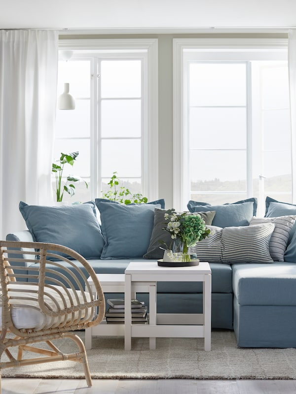 Brightly lit living room setting. Blue sofa with chaise lounge, white coffee table in front with small rattan armchair across