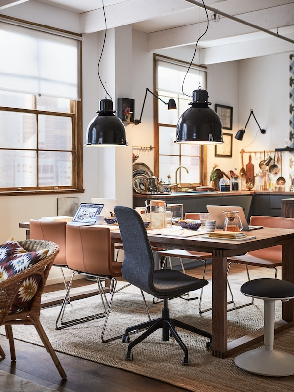 A dining room being used as a working space, with a mix of desk and dining chairs around a MÖRBYLÅNGA dining table.