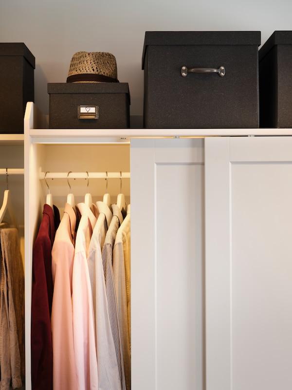 Kombinasi almari pakaian HAUGA dengan pintu gelangsar yang terbuka dan pakaian di dalamnya. Kotak berwarna hitam dan topi terletak di atas almari pakaian.