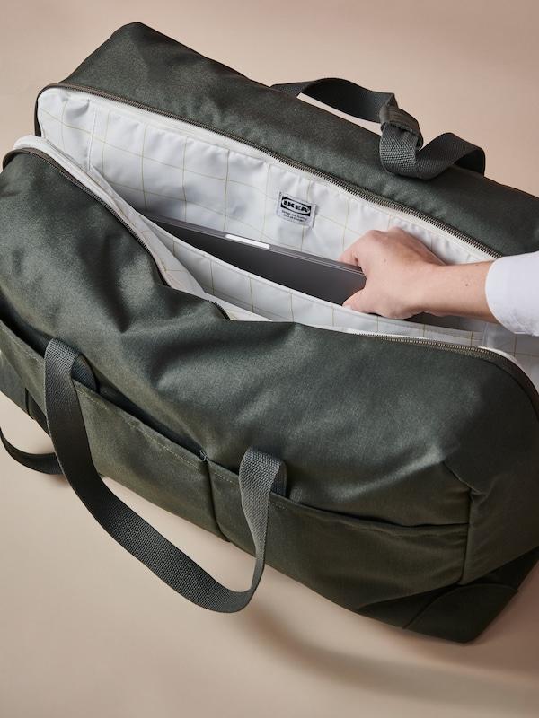 Une personne sortant un ordinateur portable d'un sac+ trousse de toilette DRÖMSÄCK vert. La doublure est dotée d'un motif à carreaux et d'une étiquette avec le logoIKEA.