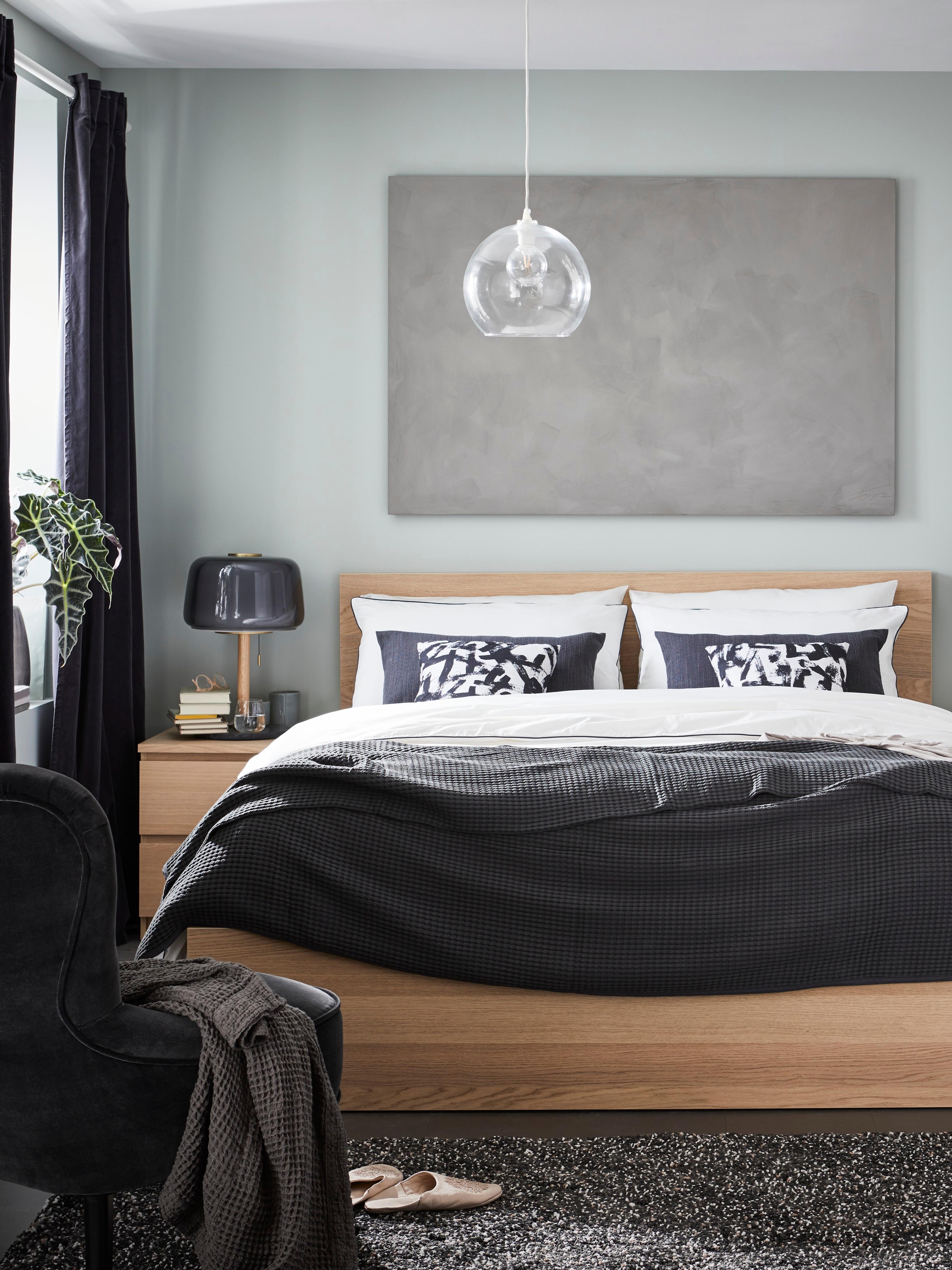 MALM visoki okvir kreveta bele boje od bajcovanog hrastovog furnira namešten je posteljinom u tamnoj i svetloj boji. Iznad njega visi siva slika.
