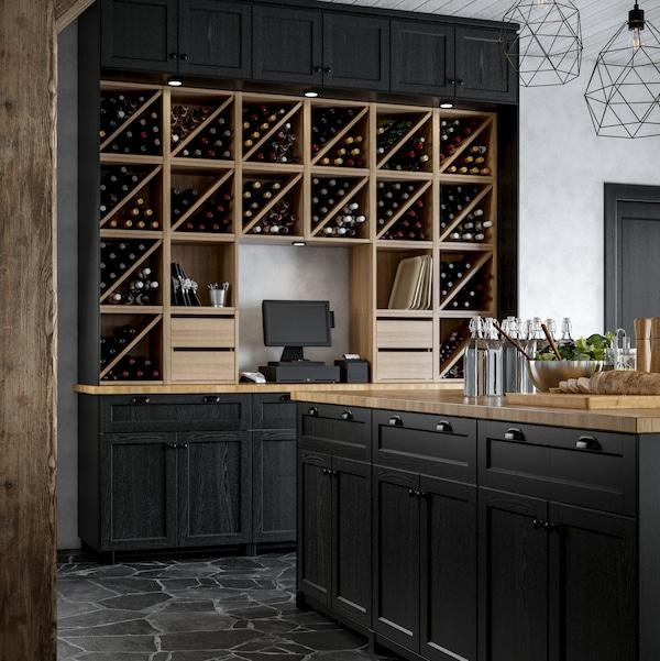 جزيرة مطبخ بأبواب طلاء أسود ورفوف زجاجات موضوعة معًا لتصميم حائط مميز وماكينة مدفوعات.
