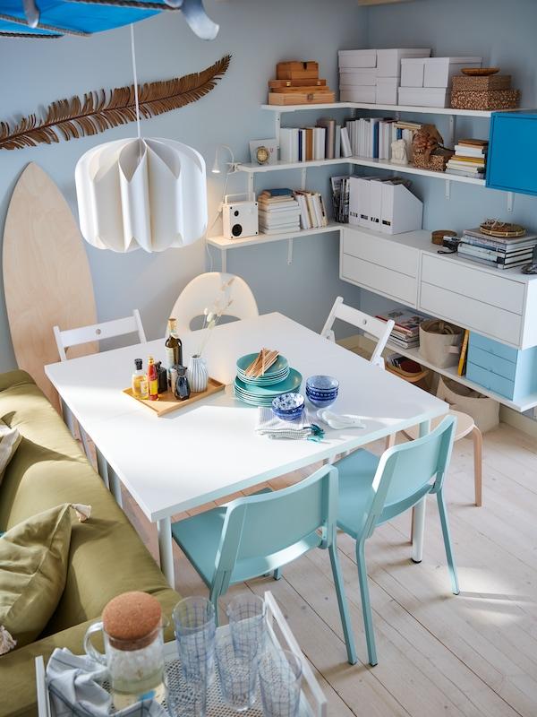 Hvidt spisebord, hvide og lys turkise stole, en hvid loftlampe, blå vægge og hvide hylder og hyldeknægte.