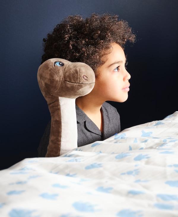 Ett barn och en mjukdjursdinosaurie som tillsammans sitter brevid sängen och tittar upp på något.