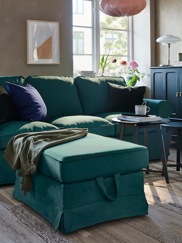 A sofa and footstool in dark turquoise, two nesting tables in dark blue-green, a rug and a dark blue-green cabinet.
