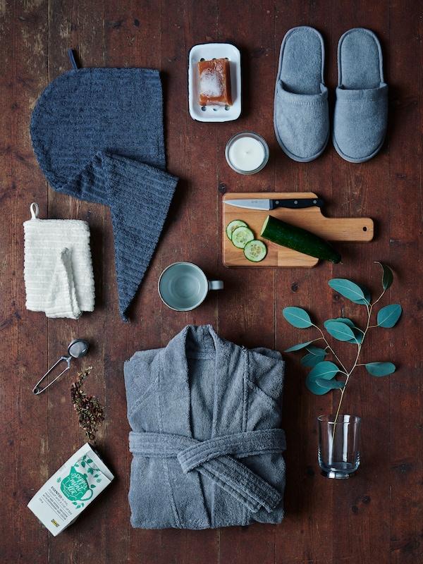 Elementele esențiale pentru o zi de spa la domiciliu, cum ar fi halat de baie ROCKÅN și ceai EGENTID, sunt așezate pe o podea din lemn de culoare închisă.