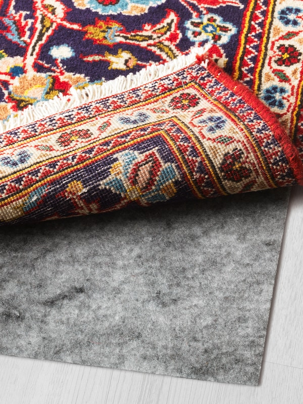 A colourful rug in shades of red, white, blue, yellow and more, with the corner turned up and a stopper underneath.