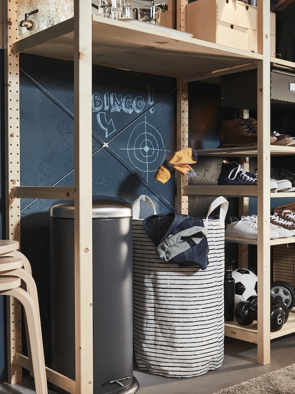 A large pedal bin and a KLUNKA laundry bag sit on the floor under a shelf in a big wooden IVAR storage combination.