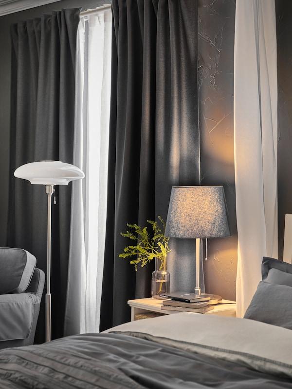 Et hvidt gardin hænger ved siden af IDANÄS seng i nærheden af en TÄLLBYN gulvlampe og en bordlampe på et sengebord.