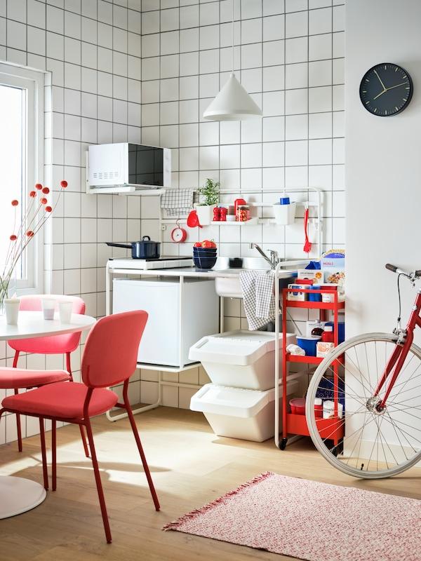 Minicucina SUNNERSTA, elettrodomestici TILLREDA, carrello rosso, tavolo con sedie rosse e bicicletta.