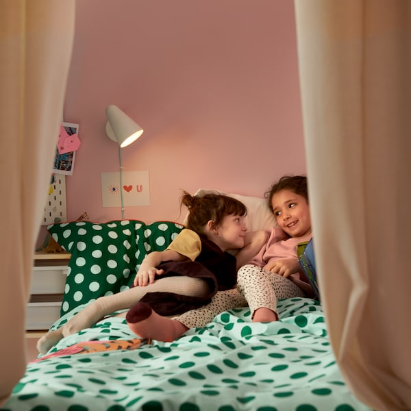 Two children lie talking on a bed with KÄPPHÄST bed linen. There are curtains around the bed and a lamp on the wall.