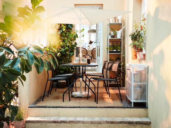 Un balcon de oraș cu jardiniere cu flori, o etajeră cu plante, ghirlandă de lumini și un loc de servit masa în stil bistro cu gustări pe masă.