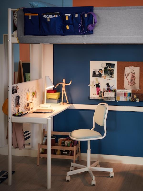 Ein hellgrauer ÖRFJÄLL Kinderschreibtischsessel unter einem Hochbett mit integriertem Schreibtisch.